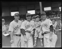 Chicago Cubs Dee Fondy, Hank Sauer, unknown child in baseball uniform, and Andy Pafko along grandstand wall at Braves Field 1951.