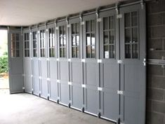 An accordion garage door idea in elegant slate gray Sectional Door, Garage Door Makeover, Garage Game Rooms, Cheap Doors, Sliding Garage Doors, Garage, Garage Door Types, Aluminium Doors, Doors