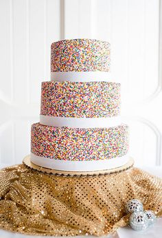 Brides.com: . Ribbons of white fondant break up the sprinkle-covered tiers of this big day dessert.