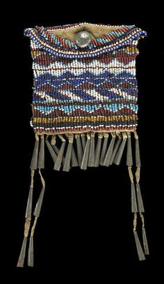 An Apache beaded strike-a-lite with fully-beaded front, partial beading on the flap and back, a lead button for closure. length 9in  (RZSQ - 6/4/07) Property from the Paul Dyck Foundation