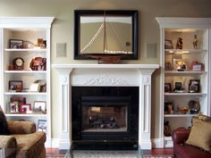 Fireplace with bookshelves on both sides. Bookshelves have lighting from the top.