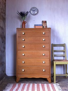 Leith Cabinet Works: Mid Century Tallboy Chest of Drawers. This chest of drawers was made around the 1950s by the British manufacturer Harris Lebus. Due to postwar restrictions in Britain at that time, this was designed in line with Utility Furniture standards, emphasising the twin values of economy and quality. The piece has been stripped of its original dark varnish to reveal golden oak, and the handle have been replaced with turned horn knobs with a humbug stripe design.