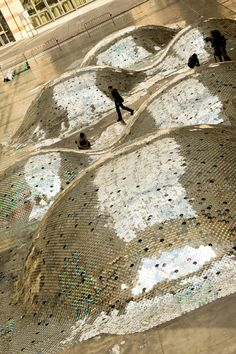 WasteLandscape takes 65,000 CDs and stretches them over 1,640 square feet of artificial knolls at Le Centquatre, an art space, in Paris.