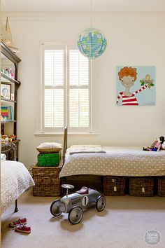 Timber plantation shutters are teamed with rattan toy boxes and traditional cast-iron beds from Ebay dressed in Adairs linen. Colour is injected with a selection of vibrant toys, a paper lantern from Vivid Room and a bright artwork by Meredith Gaston.