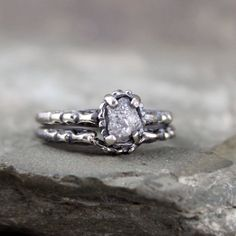 Matching engagement ring and wedding band in an oxidized antique inspired filigree style. The engagement ring is set with a natural uncut, raw, rough