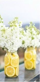 floral arrangements in mason jars with lemons in bottom