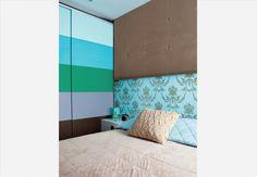 O painel de camurça esconde a parede branca e deixa o quarto mais aconchegante. Repare como o tom dele combina com as cores da parede listrada. Casa da arquiteta Letícia Arcangeli