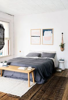 neutral bedroom with blue bedding, artwork above bed, macrame plant hanger