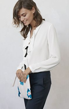 This white ruffle blouse is a great wardrobe staple. Wear it with navy trousers and a turquoise and orange floral clutch for a versatile work look | Banana Republic