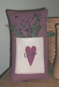 Grungy homespun pillow withstenciled pocket is about 12 x 7 inches in size. Heart is burgandy with Love stenciled in black. Aged greenery and berries are included. Great sitting on a shelf for Valentine's Day, but also nice for everyday. Fully lined and filled with high quality fiberfill. Spot clean only.