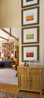 High ceilings can be a challenge when hanging art.  Choose either a vertical piece of art or hang a series of framed art going up the wall. #thegreatframeup www.thegreatframeup.com