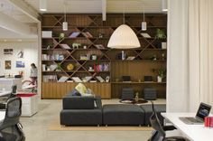 FINE Design Group Office by Boora Architects At the east end of the office, Boora designed a walnut-clad bookcase that houses an eclectic mix of books and objects. Functionally, the bookcase screens the print/copy zone, provides a touch-down spot for laptop users, and frames the lounge area. Curtains can be drawn between the lounge and open workstations to divide the space and provide visual privacy.