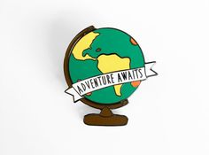 A travel inspired World Globe pin with the quote Adventure Awaits in a banner. This pin measures 30mm tall (1.2 inch) and includes a rubber