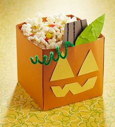 Make a Pumpkin Halloween Treat Bucket: Carve a jack-o'-lantern bucket by trimming yellow cardstock into eyes and a mouth and adhering the pieces to an orange bucket. Crumple green cardstock to add texture to a leaf and complete the project with a chenille-stem vine. X