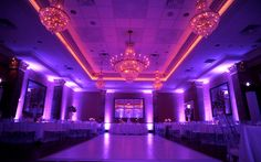 Pure Magic! This cool purple up lighting brings out the fire of those stunning chandeliers!  www.evogaevents.com