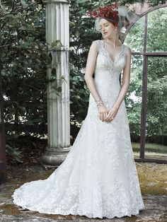Elegant lace; sparkling Swarovski crystals and pearls; and a dramatic illusion lace back make up this feminine A-line wedding dress; accented with an illusion scalloped V-neck; adorned with glamorous crystals and pearl embellishments. Lace appliques fall the length of a tulle skirt. Finished with crystal buttons over zipper closure.