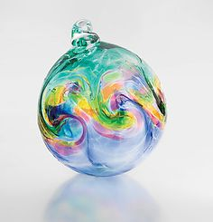 """Big Sur""   Tom Stoenner     Frosty blue-green colors dance over a blown glass globe, with iridescent chips of glass adding a sparkle of glistening texture.                                                                                                            Cresting waves are robed in the colors of sunset, beautifully created in  blown glass."