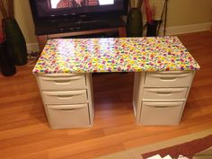 My craft table. Plywood covered in fun duct tape. Cheap surface I don't mind destroying and when I get tired of it, I switch it up. Took just a little more than one roll. At $3.50 a roll, plus two file cabinets on clearance ($15 each) that's a craft table I can afford!