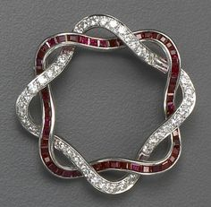 A retro ruby, diamond and platinum brooch, circa 1945  of openwork design, with two interlocking scalloped square links, one set with calibré-cut rubies, the other with round brilliant-cut diamonds; estimated total diamond weight: 1.20 carats; estimated total ruby weight: 1.20 carats.
