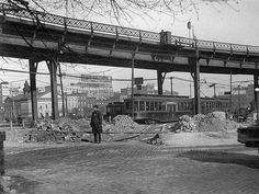 A lone policeman guards the end of the trolley line on Roebling Street at the Williamsburg Bridge plaza. A stack of cobblestones and a man rolling a new tire behind him. Brooklyn, New York.  1921