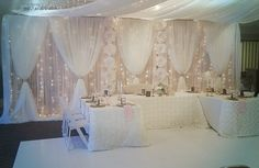 Moments In Time Wedding & Event Rentals table front, head table backdrop and ceiling drape dressed with ivory voile, fairy lights, icicle lights, paper flowers, blush voile, champagne glitter cuffs.