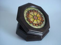 Caixa de madeira, oitavada redonda, revestida externamente em decapê escuro e com tampa trabalhada em vitral. <br>Forradas internamente.
