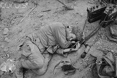 25 Nov 1967, Near Dak To, South Vietnam --- Hill 875, South Vietnam: The tumult of the battle over, Sgt. John G. Sheehan of Boston, Mass., radio still attached on and pressed to his ear, takes well-earned rest atop Hill 875 following its capture by elements of the 173rd Airborne Brigade. Conquest of Hill 875 ended five days of the bitterest fighting of the Vietnam War. --- Image by © Bettmann/CORBIS