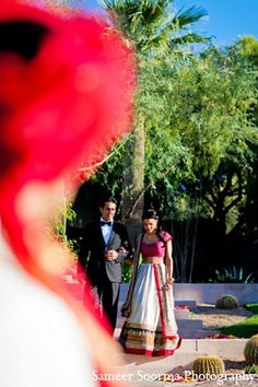 An Indian bride and groom wed in outdoor ceremony in Arizona. They choose a traditional Indian theme for their wedding while opting for a more modern approach to their reception in a white dress and tuxedo.