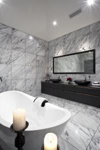 Interior designer Peta Teal has clad all the walls and the floor of the ensuite bathroom in Carrara marble tiles to enhance the spaciousness of the room by creating an open and uncluttered look.