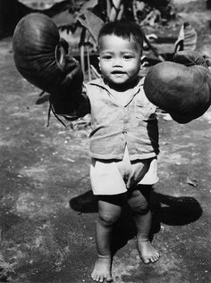 A young boy on Leyte Island in the Philippines with a pair of boxing gloves that an American soldier had given him.