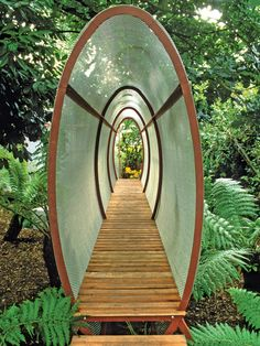 This unusual wire mesh tunnel, a work of art in itself, invites use and functions as both a screen and a walkway.