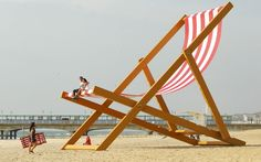 A couple sit it what is expected to be confirmed as the world's largest deckchair on Bournemouth Beach. The deck chair measures eight and a half metres tall by five and a half metres wide, and weighs almost six tonnes. This has been commissioned by Pimm's to mark British Summer Time. Clocks will go forward by one hour on Sunday.