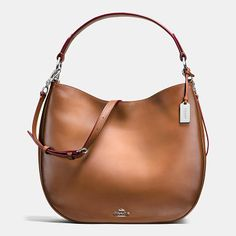nomad hobo by COACH. Soft and slouchy in burnished glovetanned leather, this simple, graceful silhouette is dressed up with striking hardw...
