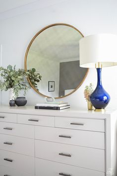 Transitional-modern-style-bedroom-decor-black-and-white-modern-vases-round-gold-mirror-navy-and-gold-lamp-modern-gray-dresser-with-brass-hardware-2.
