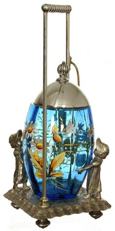 Ten-inch pickle castor having a blue art glass egg-shaped insert with enamel floral décor, on a Tufts silverplate frame. Glass Dishes, Glass Jars, Date, Brides Basket, Condiment Sets, Pickle Jars, Decorated Jars, Himmelblau, Duck Egg Blue