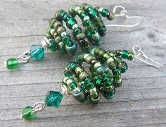 """Stunning lantern style hand beaded earrings in shades of green, with sterling silver ear wires. This is what happened when I was faced with a challenge pack containing bead cages and seed beads, neither of which I would usually use...I found a way to use them both together, then got hooked and made more! They hang approx. 2"""" (5cm) from the ear wire, and they're approx. 3/4"""" (2cm) wide at the widest part of the lantern. Includes a green Swarovski crystal as part of the dangle.  $12.50"""