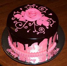Vanilla cake filled with whip cream, frosted in buttercream. Airbrushed in hot pink. Drizzled with dark chocolate lacquer. Buttercream pink filigree / scrolls and topped with a hot pink rose