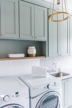 Exquisitely designed green gray laundry room is lit by a brass and glass lantern. Exquisitely designed green gray laundry room is lit by a brass and glass lantern. Exquisitely designed green gray laundry room is lit by a brass and glass lantern. Laundry Room Cabinets, Laundry Room Organization, Laundry Room Design, Diy Cabinets, Laundry Storage, Kitchen Cabinets, Modern Laundry Rooms, Laundry Room Inspiration, Green Cabinets