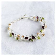 Wouldn't you love people to notice this gorgeous bracelet on your arm? This lacy and crocheted sterling silver bracelet is part of a set. It features, real citrines, faceted garnets and Swarovski crystals. To see it, head to my website store: https://www.andiclarkejewelry.com/