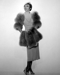 """Blue gray wool crepe is used in fashioning this attractive fall costume for Claudette Colbert. Two inverted pleats give the necessary fullness at the bottom of the skirt, and a tiny square neck with rows of self-covered buttons lends a new note. Bands of gray fox form the sleeves and a muff of the same fur is carried. A beret-like hat of the dress material, with kid gray kid slippers, complete the costume""."