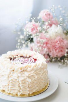 Foto clean em tons claros e bem iluminada. Chiffon Maria Antonieta com flores rosas e brancas (mosquitinho e cravos) em uma mesa branca.