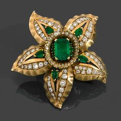 "RENé BOIVIN YEARS 1940 CLIP ""Narcissus"" (SPECIAL ORDER) It represents a flower with five petals adorned the center of a rectangular emerald cut sides carved degrees. Repercées the leaves are set with brilliant cut diamonds and emeralds pears. Mount 18K yellow gold satin. French Labour party hallmark deleted."