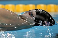 Surface tension creates a glassy, smooth layer of water over U.S. swimmer Tyler Clary the instant before he surfaces as he competes in the backstroke. (Photo credit: Getty Images)