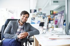 Happy businessman sitting at desk in office