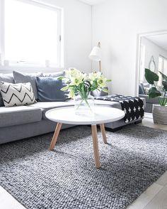 Biało-szary salon z dekorację poduszkami i kwiatami