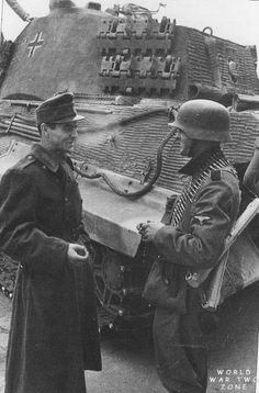 With a Tiger II as a backdrop, a Waffen SS machine gunner and Hungarian solider pause for a smoke in Budapest, December, 1944 - http://worldwartwozone.com/forums/index.php?/topic/6273-tiger-ii-power-on-the-prowl/page-2