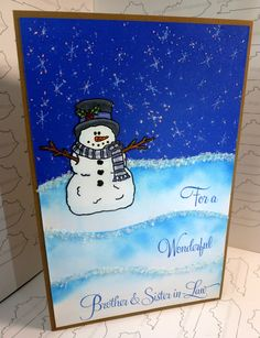 "A handmade Winter, Christmas Card measuring 8 1/2"" x 5 1/2""; and using Cardstock - Recollections 65lb white, blue, kraft; Stamps - High Hopes stamps: Gimme A Hug! Snowman, Snow Background; Kitchen Sink Stamps: Whole Family;  Ink - Gina K Color Companions: Black Onyx, White; Distress Inks: Broken China; Memento: Danube Blue; Color - Copics Accessories - Stickles: Diamond; Recollections: Red, Black; Martha Stewart glitter: snow"