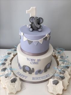 Two tier first birthday cake with elephant theme, blue, white and grey colour scheme and matching cookies.