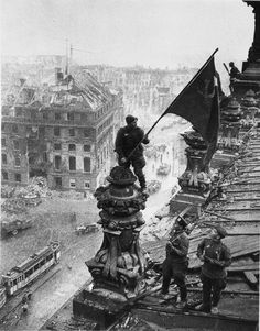 Another, earlier view of the famous photograph by Yevgeny Khaldei showing Russian soldiers raising the flag of the Soviet Union on top of the German Reichstag building following the Battle of Berlin. The later, more familiar photo showing the actual flag-raising was embroiled in controversy over its staging, the identities of the soldiers, the photographer, and some photo editing.