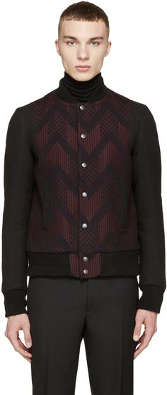 Long sleeve bomber jacket in black. Woven pattern throughout body in tones of burgundy and indigo. Ribbed knit stand collar, cuffs, and hem. Press-stud closure and welt pockets at front. Welt pockets at interior. Quilted lining. Tonal stitching.